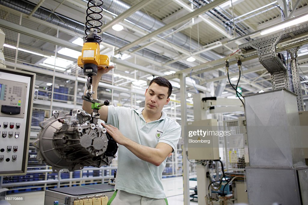 An employee positions an MQ100 transmission assembly on the automobile production line at Skoda Autos AS in Mlada Boleslav, Czech Republic, on Friday, March 15, 2013. VW, which also owns the Porsche luxury-auto brand as well as the Skoda and Seat volume marques, will build at least 10 plants globally, including seven in China, Martin Winterkorn, chief executive officer of Volkswagen AG, said. Photographer: Martin Divisek/Bloomberg via Getty Images