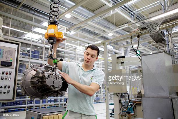 An employee positions an MQ100 transmission assembly on the automobile production line at Skoda Autos AS in Mlada Boleslav Czech Republic on Friday...
