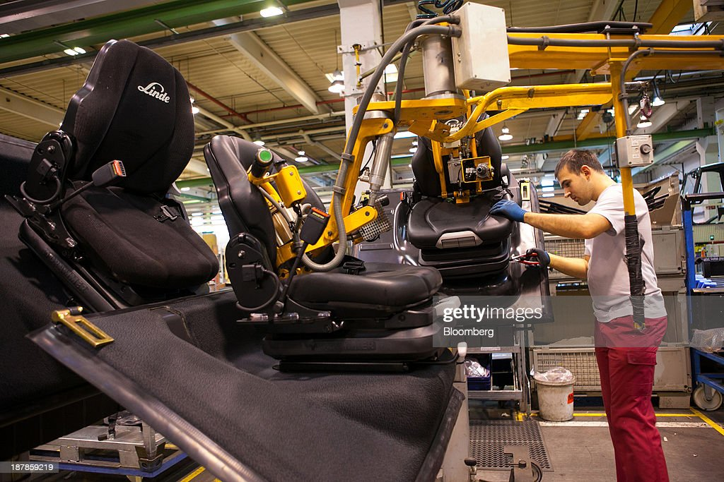 An employee positions seating into a Linde H30 forklift truck as its sits on the production line at the Linde Material Handling GmbH factory, a unit of Kion Group AG, in Aschaffenburg, Germany, on Tuesday, Nov. 12, 2013. Kion Group AG, the German forklift-maker which listed shares in June, is looking to expand its global sales network via acquisitions to catch up with main competitor Toyota Industries Corp. Photographer: Krisztian Bocsi/Bloomberg via Getty Images