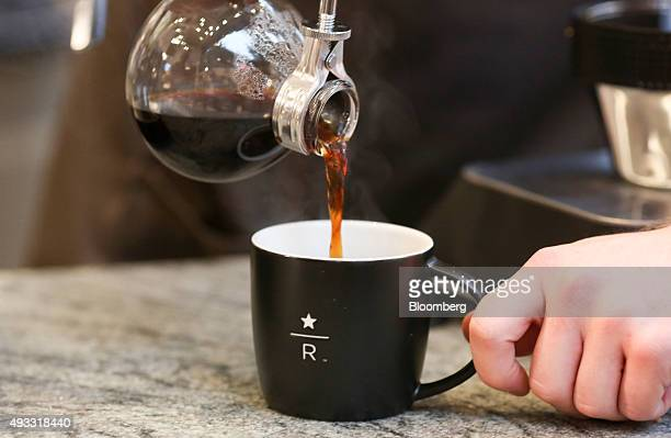 An employee pours a cup of coffee into a Reserve cup used for specialist coffee at a Starbucks Corp coffee shop in London UK on Friday Oct 16 2015...