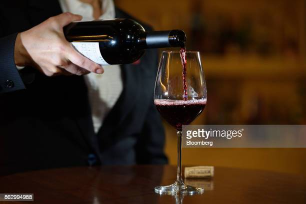 An employee pours a glass of wine at the Amazon Bar operated by Amazon Japan KK during a media preview in Tokyo Japan on Thursday Oct 19 2017 For 10...
