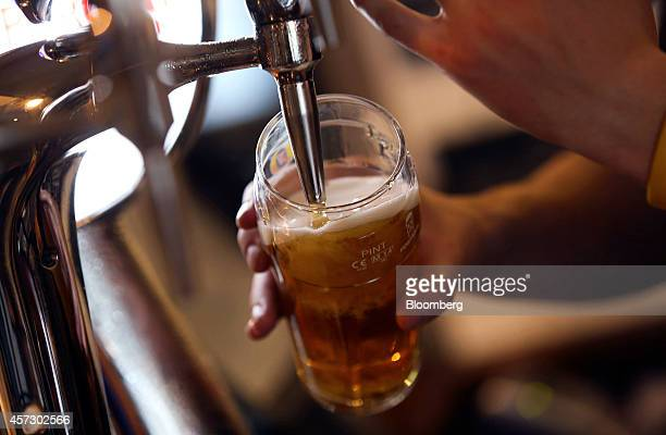 An employee pours a pint of Fosters lager produced by Heineken NV inside the Paul Pry pub operated by John Barras a unit of Spirit Pub Co in Rayleigh...