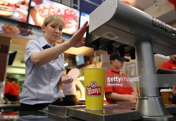 An employee pours a serving of soft drink for a customer behind the service counter of a Wendy's fast food restaurant in Moscow Russia on Friday...