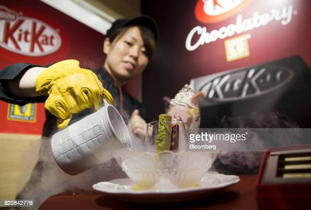 An employee pours liquid nitrogen into a bowl while serving a frozen KitKat dessert during a media preview of the KitKat Chocolatory Ginza store...