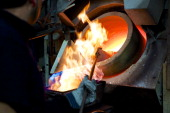 An employee pours molten silver from a crucible into a one kilogram mould during the semiautomated gold and silver bar manufacturing process at a...