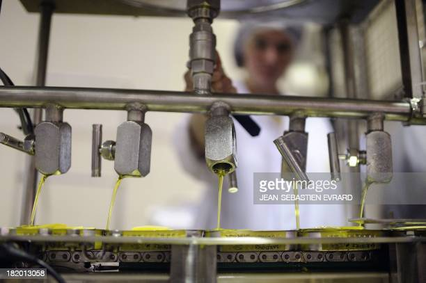 An employee pours olive oil in a tin of sardines on September 25 2013 in Quiberon western France at the canning factory 'La Belle Iloise' The company...