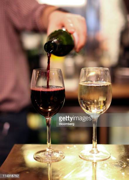 An employee pours red wine into a glass at an All Bar One bar operated by Mitchells Butlers Plc in London UK on Tuesday May 17 2011 Food and alcohol...