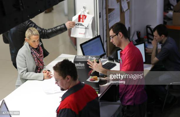 An employee prepares a Braun product for a customer at the service counter of a fulfilment center operated by Ulmart Russia's largest online...