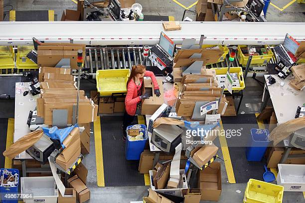 An employee prepares a cardboard box ready for distribution at the Amazoncom Inc fulfillment center in Hemel Hempstead UK on Wednesday Nov 25 2015...