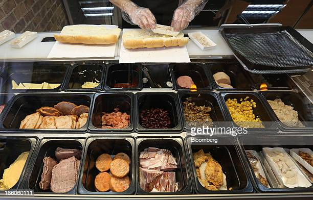 An employee prepares a customer's sandwich order at the food counter of a Subway fast food restaurant in Moscow Russia on Sunday April 7 2013...