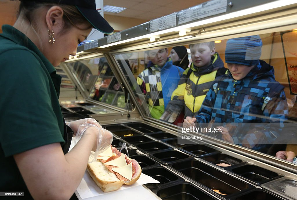 An employee prepares a customer's sandwich order at the food counter of a Subway fast food restaurant in Moscow, Russia, on Sunday, April 7, 2013. McDonald's, which virtually created the market for burgers and fries in the country and convinced Russians it's OK to eat with their hands, must fend off a growing challenge from rivals Burger King Worldwide Inc., Subway Restaurants, Yum! Brands Inc. and Wendy's Co. Photographer: Andrey Rudakov/Bloomberg via Getty Images