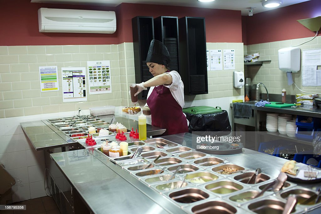 An employee prepares a customer's sanwdwich order in the kitchen of a 100 Montaditos restaurant in Madrid, Spain, on Wednesday, Nov. 21, 2012. The Madrid-based chain in January opened its first U.S. restaurant in Miami and aims to have eight outlets in Florida by next March. Photographer: Angel Navarrete/Bloomberg via Getty Images