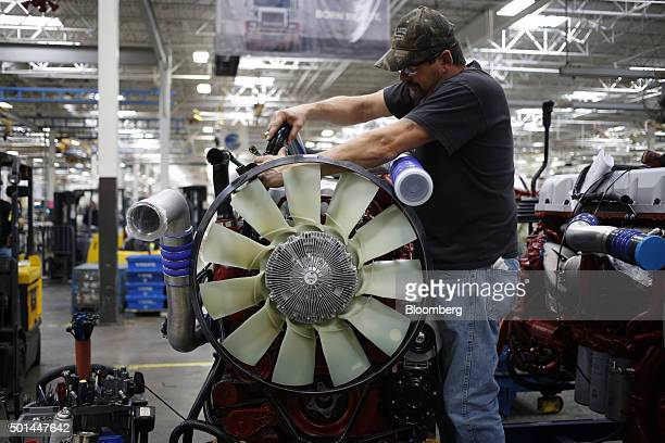 An employee prepares a diesel engine for installation into a truck at the Mack Truck Inc cab and vehicle assembly plant in Macungie Pennsylvania US...