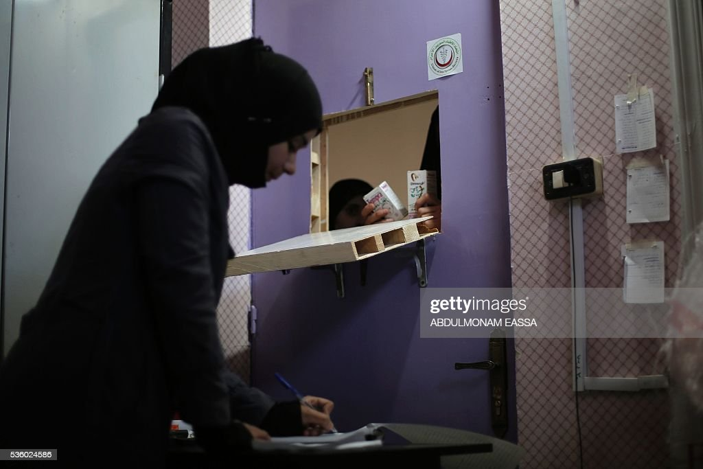 An employee prepares a drug order in the pharmacy of a clinic run by a local non-profit organisation called the Union of Free Syrian Doctors, in the rebel-controlled Syrian village of Utaya, in the eastern Ghouta region on the outskirts of the capital Damascus, on May 31, 2016. The non-government organisation offers medical services in the area in the absence of public services provided the state. / AFP / ABDULMONAM