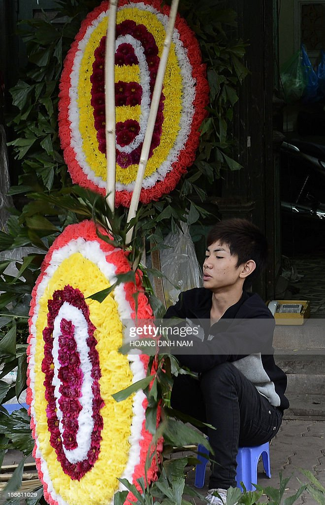 An employee prepares a funeral wreath for a customer at a funeral supplies shop which also sells coffins in Hanoi on December 21, 2012. Vietnam has imposed strict limits on the number of wreaths that can be laid at officials' funerals and banned civil servants from burning 'ghost money' in a bid to assuage public anger over government waste. AFP PHOTO/HOANG DINH Nam