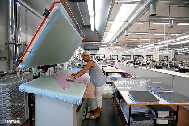 An employee prepares a garment on the bed of an industrial press during the manufacturing stages inside Brunello Cucinelli SpA's production facility...