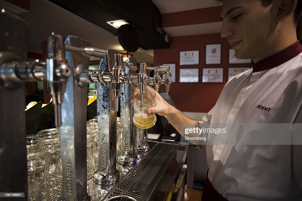 An employee prepares a glass tankard of beer behind the bar of a 100 Montaditos restaurant in Madrid, Spain, on Wednesday, Nov. 21, 2012. The Madrid-based chain in January opened its first U.S. restaurant in Miami and aims to have eight outlets in Florida by next March. Photographer: Angel Navarrete/Bloomberg via Getty Images