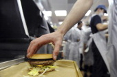 An employee prepares a hamburger at a US fast food Mac Donalds restaurant on December 1 2011 in RamonvilleSaintAgne a Toulouse suburb southern France...