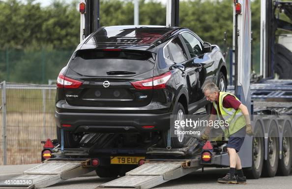 An employee prepares a new Nissan Qashqai SUV automobile produced by Nissan Motor Co ahead of delivery to Toomey Motor Group's car dealership in...