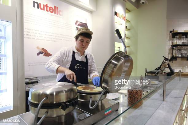 An employee prepares a pancake with Nutella spread inside the new Eataly food store operated by Eataly Net Srl at the Kievsky shopping mall in Moscow...