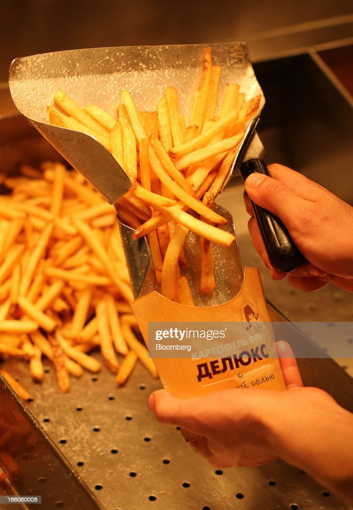 An employee prepares a portion of french fries for a customer in the kitchen area of a Wendy's fast food restaurant in Moscow, Russia, on Friday, April 5, 2013. McDonald's, which virtually created the market for burgers and fries in the country and convinced Russians it's OK to eat with their hands, must fend off a growing challenge from rivals Burger King Worldwide Inc., Subway Restaurants, Yum! Brands Inc. and Wendy's Co. Photographer: Andrey Rudakov/Bloomberg via Getty Images
