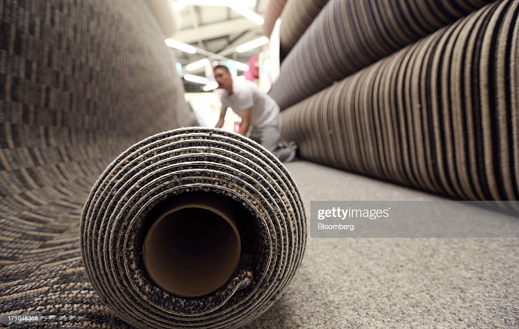 An employee prepares a roll of carpet ahead of cutting for a customer inside a Carpetright Plc store in Basildon, U.K., on Friday, June 21, 2013. U.K. retail sales rose more than economists forecast in May as consumers spent more online and food sales increased at their fastest pace for more than two years. Photographer: Chris Ratcliffe/Bloomberg via Getty Images