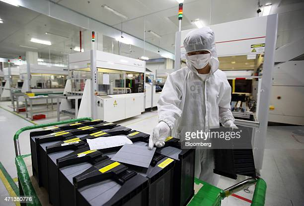 An employee prepares a solar cell before loading it into a machine on the production line at the Trina Solar Ltd factory in Changzhou Jiangsu...