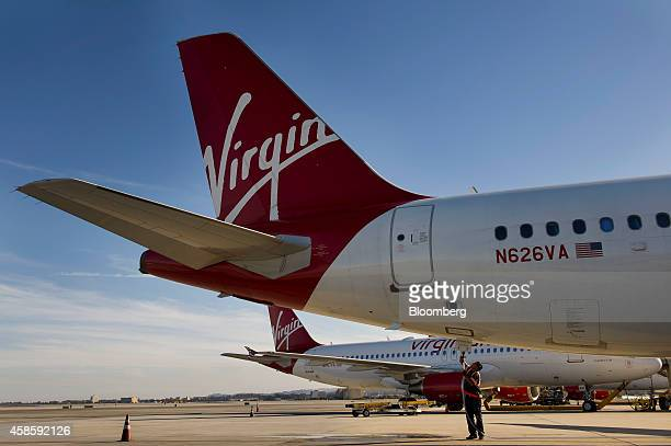 An employee prepares a Virgin America Inc Airbus A320 plane for take off at San Francisco International Airport in San Francisco California US on...