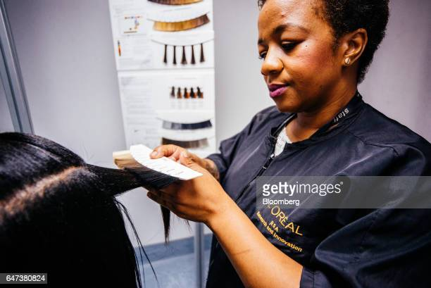 An employee prepares a visitor's hair during research in the haircare salon at the new L'Oreal SA Research and Innovation Center in Johannesburg...