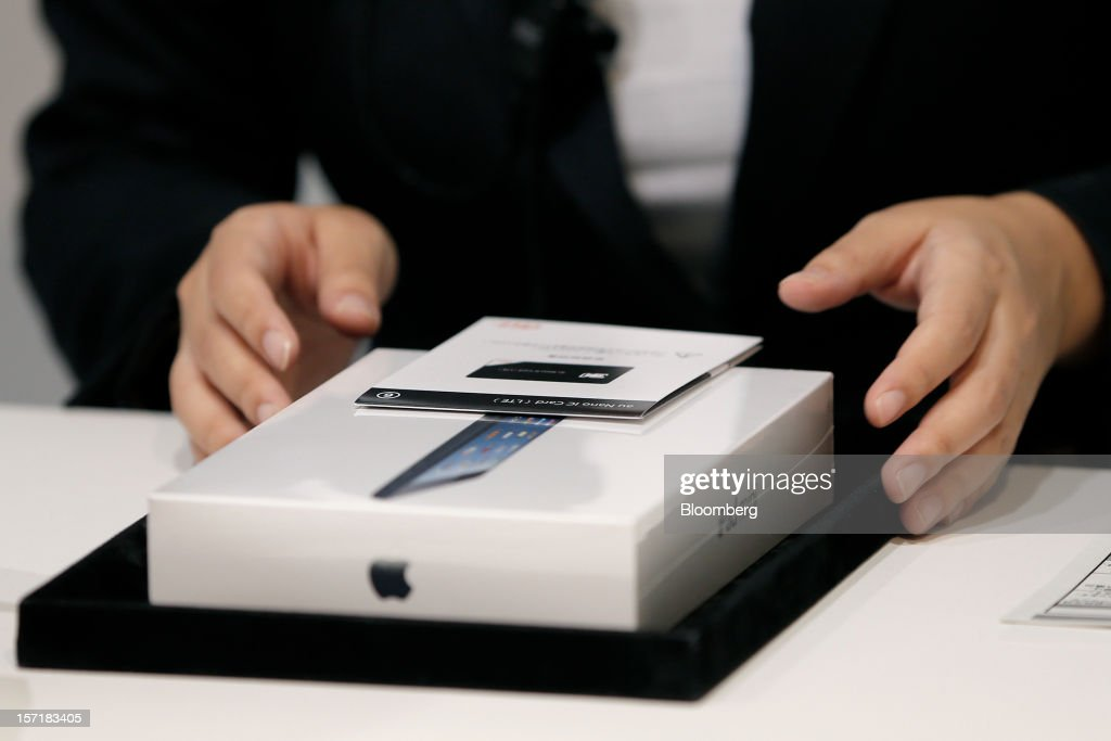 An employee prepares an Apple Inc. iPad Mini for a customer at a KDDI Corp. store in Tokyo, Japan, on Friday, Nov. 30, 2012. The iPad Mini went on sale at KDDI and Softbank Corp. stores in Japan today. Photographer: Kiyoshi Ota/Bloomberg via Getty Images