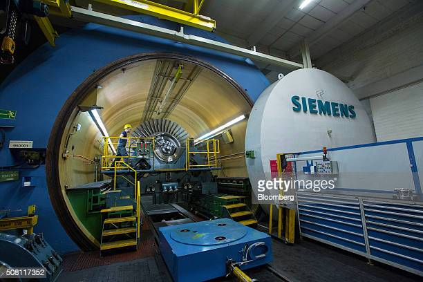 An employee prepares an Fclass turbine in the vacuum testing facility at Siemens AG's gas turbine factory in Berlin Germany on Tuesday Feb 2 2016...