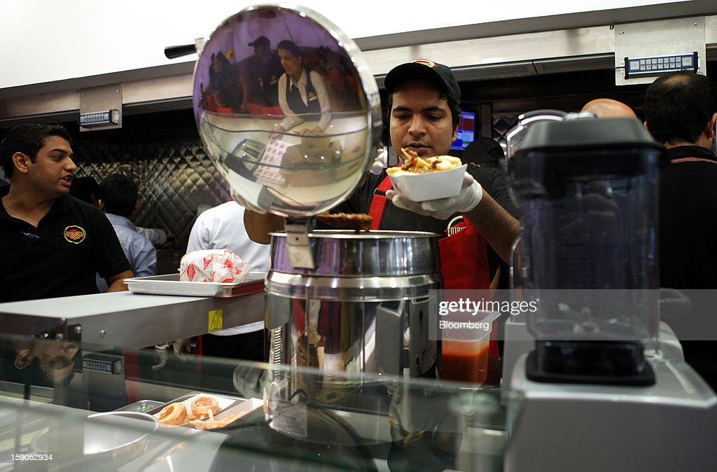 An employee prepares an order in the kitchen area of a Fatburger outlet in Karachi, Pakistan, on Saturday, Jan. 5, 2013. Fatburger opened its first outlet in Pakistan to the public on Jan. 5. Photographer: Asim Hafeez/Bloomberg via Getty Images