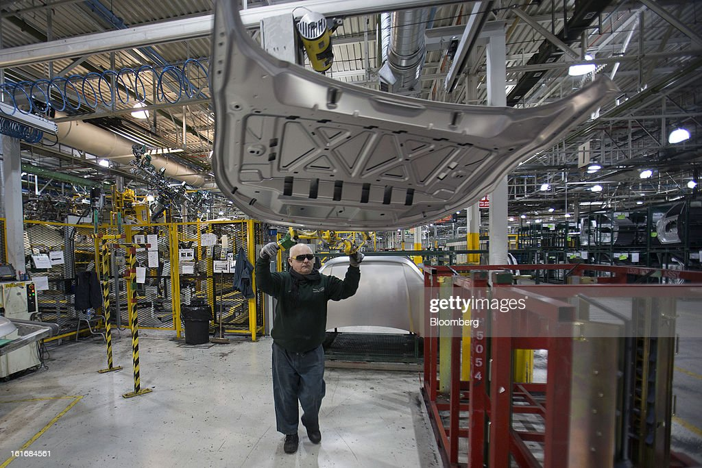 An employee prepares an unpainted aluminum hood for a Range Rover Evoque SUV automobile, produced by Jaguar Land Rover Plc, a unit of Tata Motors Ltd., at the company's assembly plant in Halewood, U.K., on Wednesday, Feb. 13, 2013. Carmakers from Ford Motor Co. to Audi AG and Jaguar Land Rover Plc are using record amounts of aluminium to replace heavier steel, providing relief to producers of the metal confronting excess supplies and depressed prices. Photographer: Simon Dawson/Bloomberg via Getty Images
