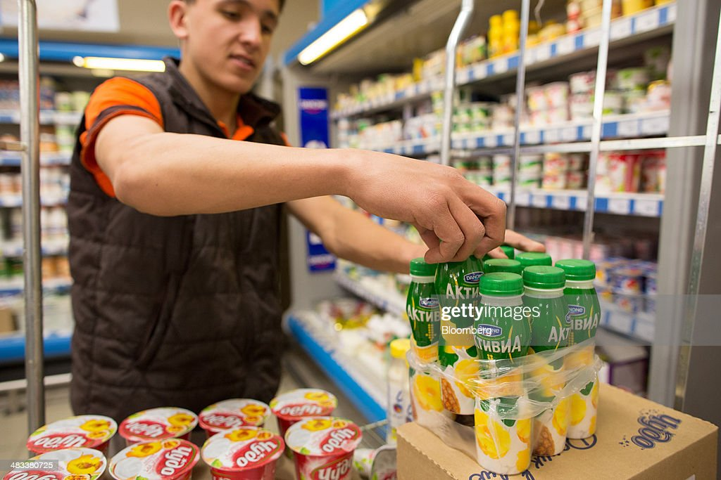 An employee prepares bottles of Danone SA yoghurt drinks for sale as he restock a sales display inside a Dixy supermarket operated by OAO Dixy Group in Moscow, Russia, on Tuesday, April 8, 2014. Suppliers suffering from ruble depreciation this quarter are urging retailers to increase prices. Photographer: Andrey Rudakov/Bloomberg via Getty Images