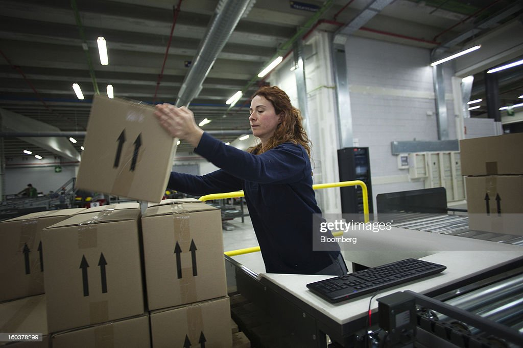 An employee prepares boxes of pharmaceutical products for distribution to customers at the Cofares SA logistical plant in Guadalajara, Spain, on Wednesday, Jan. 30, 2013. Madrid, the second-biggest contributor to Spain's economy after Catalonia, has sliced 1 billion euros from its budget in 2012, increasing public-transportation costs and university fees, cutting jobs, delaying investments and reducing health-care and social benefits. Photographer: Angel Navarrete/Bloomberg via Getty Images