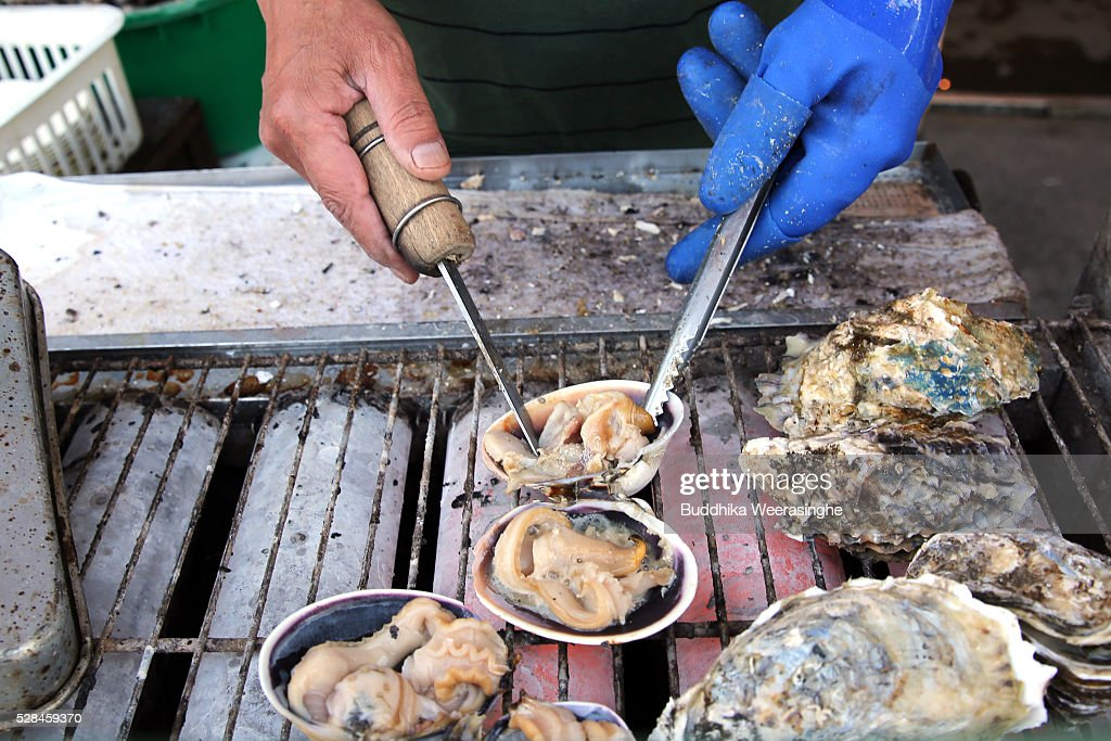 An employee prepares clams for barbecue on a road side stall at Okage Yokocho, a traditional shopping street on May 5, 2016 in Ise, Japan. Ise-Shima prepares for the G7 summit which is to be held on May 26 and 27, 2016.