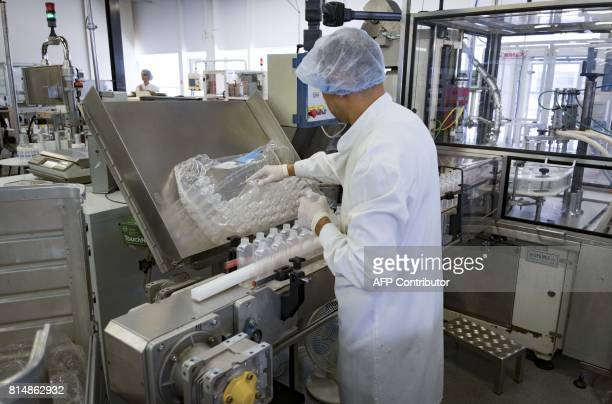 An employee prepares empty containers for cosmetic products on a production line at the plant of French multinational pharmaceutical and cosmetics...