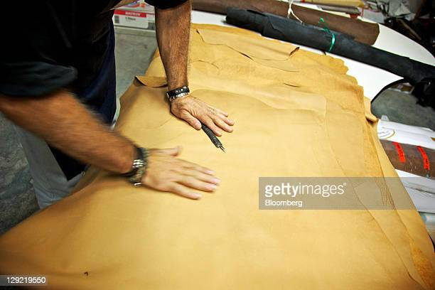 An employee prepares leather used in the manufacture of shoes for the Oliver Sweeney brand at a factory in Corridonia Italy on Thursday Oct 13 2011...