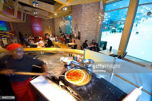 An employee prepares pizza at 'Apres' a cocktail lounge bar and restaurant at Ski Dubai at the Mall of the Emirates in Dubai United Arab Emirates...