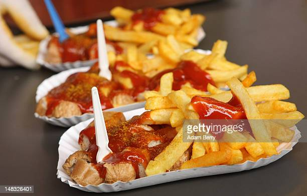 An employee prepares plates of currywurst with french fries at Konnopke's currywurst stand on July 14 2012 in Berlin Germany Currywurst originally...