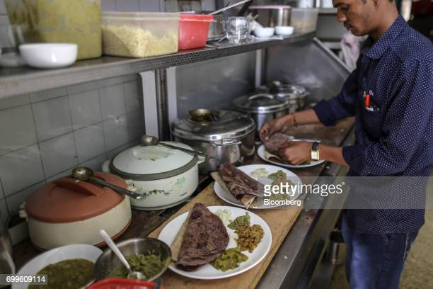 An employee prepares plates of food at the Vaathsalya Millet Cafe in Bengaluru India on Saturday June 10 2017 Millets were a staple in India for...