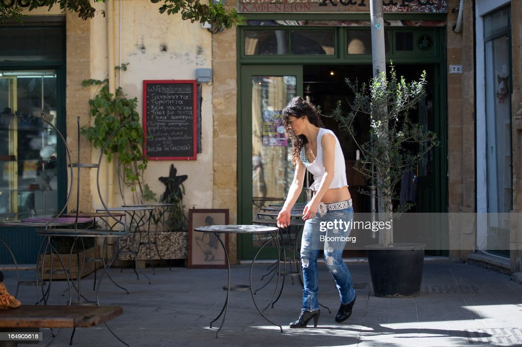 An employee prepares the outside terrace area of a cafe ahead of opening in Nicosia, Cyprus, on Friday, March 29, 2013. Cypriots face a second day of bank controls over their use of the euro as officials in Europe urged the country to move quickly to lift the restrictions, the first time they have been imposed on the common currency. Photographer: Simon Dawson/Bloomberg via Getty Images
