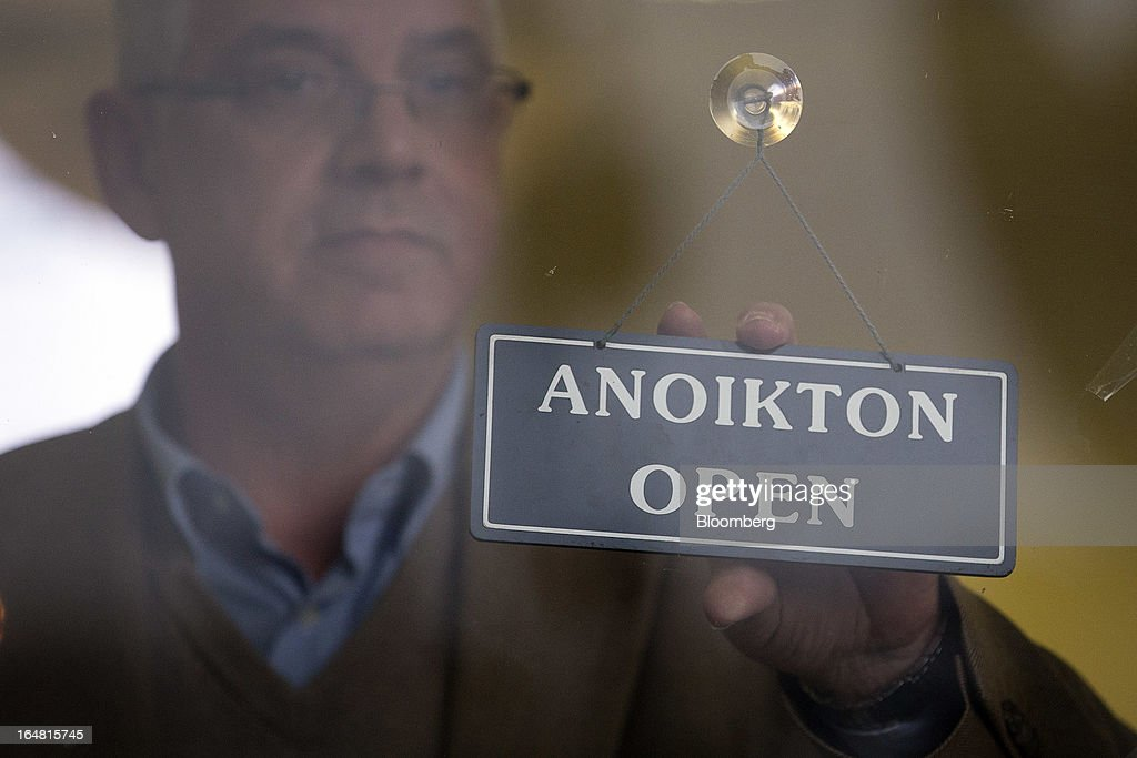 An employee prepares to change the open sign to closed at a Bank of Cyprus Plc branch as banks open for the first time in two weeks in Nicosia, Cyprus, on Thursday, March 28, 2013. The Central Bank of Cyprus's capital controls will include a 300-euro ($383) daily limit on withdrawals and restrictions on transfers to accounts outside the country. Photographer: Simon Dawson/Bloomberg via Getty Images