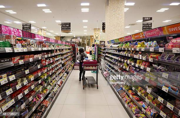 An employee prepares to display sweets at an Aeon Co supermarket in Chiba Japan on Monday March 31 2014 The country's consumption tax is being raised...