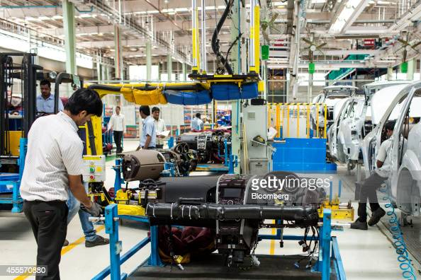 An employee prepares to fit the dashboard of Mahindra Mahindra Ltd XUV 500 sportutility vehicles on the production line at the company's facility in...