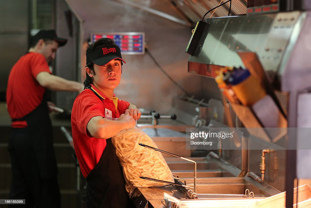 An employee prepares to fry a bag of raw potato french fries in the kitchen area of a Wendy's fast food restaurant in Moscow, Russia, on Friday, April 5, 2013. McDonald's, which virtually created the market for burgers and fries in the country and convinced Russians it's OK to eat with their hands, must fend off a growing challenge from rivals Burger King Worldwide Inc., Subway Restaurants, Yum! Brands Inc. and Wendy's Co. Photographer: Andrey Rudakov/Bloomberg via Getty Images