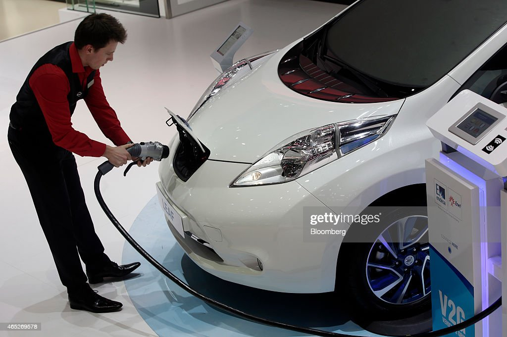 An employee prepares to install a charging plug in the socket of a Nissan Leaf electric automobile on day two of the 85th Geneva International Motor...