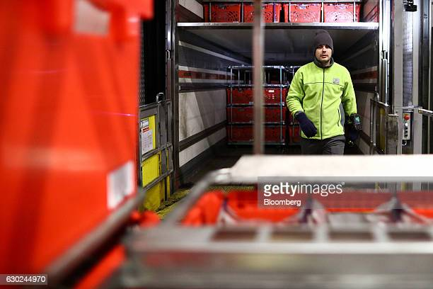 An employee prepares to load a trolley of completed customer order crates on to a delivery vehicle at the Ocado Group Plc distribution centre in...