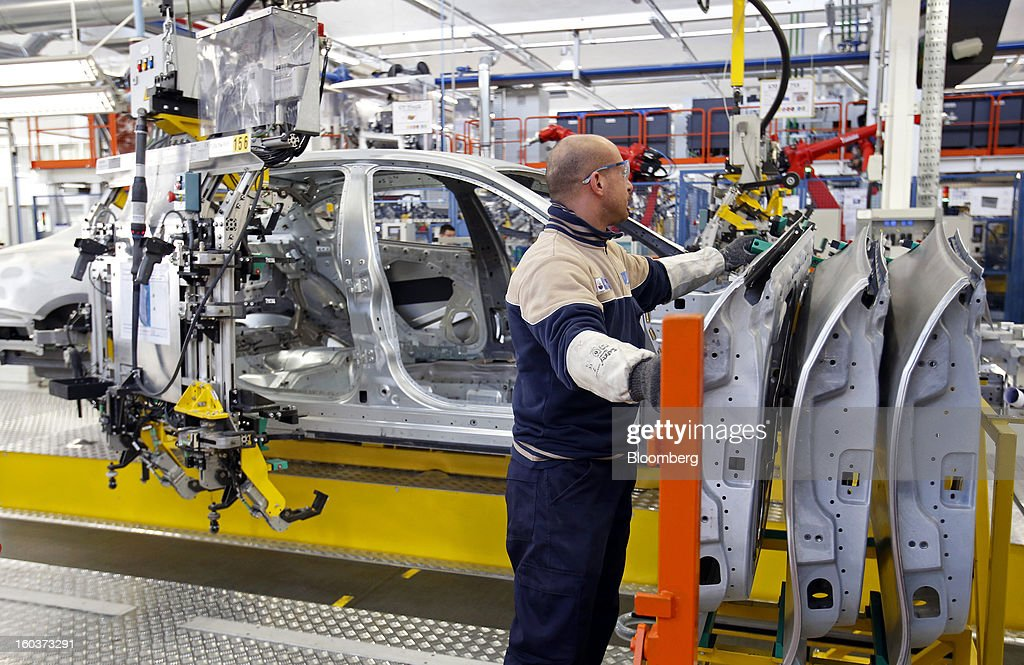 An employee prepares to mount a rear passenger door onto the bodyshell of a Maserati Quattroporte luxury automobile as it travels along the production line at Fiat SpA's Grugliasco factory in Turin, Italy, on Wednesday, Jan. 30, 2013. Fiat SpA Chief Executive Officer Sergio Marchionne said the Italian carmaker narrowed losses in Europe in the fourth quarter, helping it achieve full-year earnings that were in line with its forecasts. Photographer: Alessia Pierdomenico/Bloomberg via Getty Images