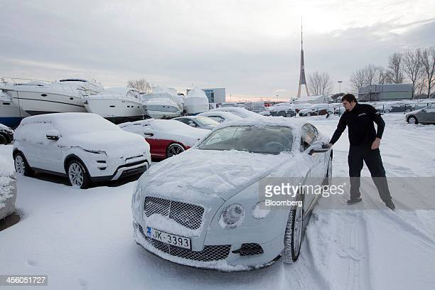 An employee prepares to move a luxury Bentley GT automobile into the workshop at the Bentley Motors Ltd dealership in Riga Latvia on Tuesday Dec 10...